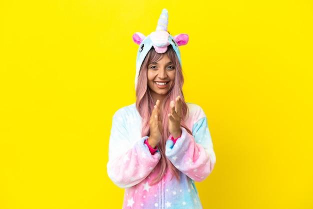 Giovane donna di razza mista che indossa un pigiama unicorno isolato su sfondo bianco che applaude dopo la presentazione in una conferenza
