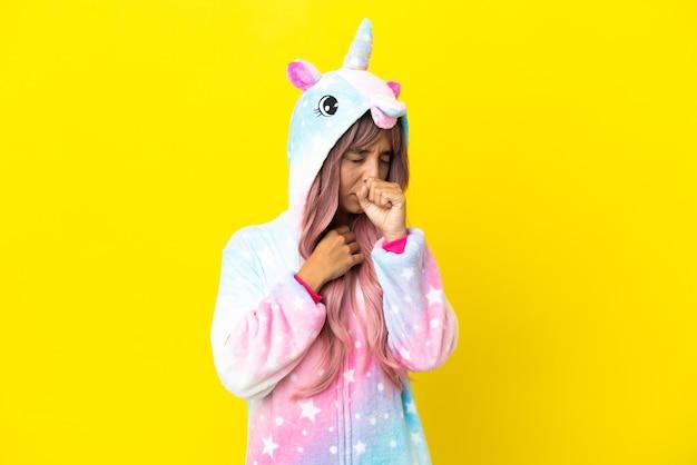 La giovane donna di razza mista che indossa un pigiama unicorno isolato su sfondo bianco soffre di tosse e si sente male