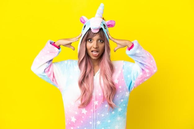 Giovane donna di razza mista che indossa un pigiama unicorno isolato su sfondo bianco con espressione a sorpresa