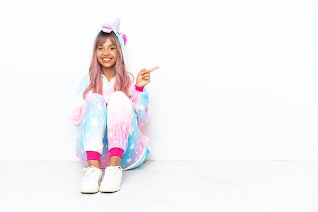 Giovane donna di razza mista che indossa un pigiama di unicorno seduto sul pavimento isolato su sfondo bianco che punta il dito verso il lato