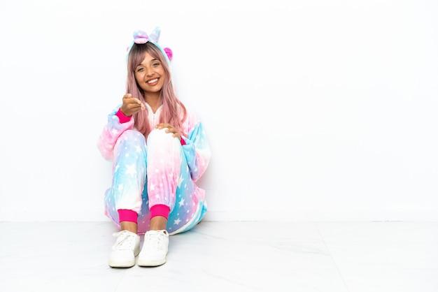 Giovane donna di razza mista che indossa un pigiama di unicorno seduto sul pavimento isolato su sfondo bianco che stringe la mano per chiudere un buon affare