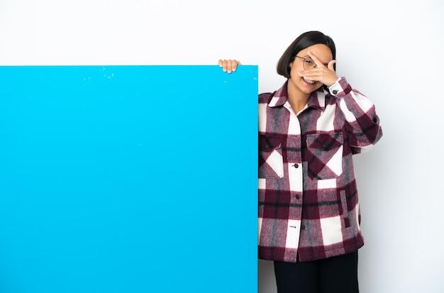 Giovane donna di razza mista con un grande cartello blu isolato su sfondo bianco che copre gli occhi con le mani e sorridente