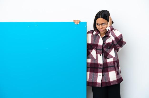 Giovane donna di razza mista con un grande cartello blu isolato su sfondo bianco frustrato e che copre le orecchie