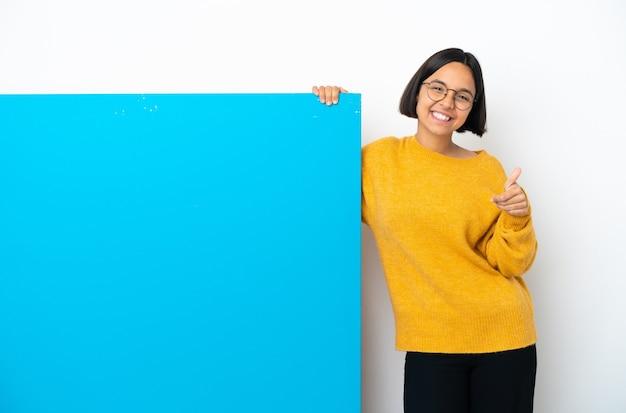 Giovane donna di razza mista con un grande cartello blu isolato su sfondo bianco che tiene immaginario copyspace sul palmo per inserire un annuncio e con il pollice in alto