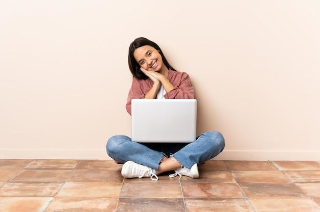 La giovane donna di razza mista con un laptop seduto sul pavimento tiene insieme il palmo. la persona chiede qualcosa