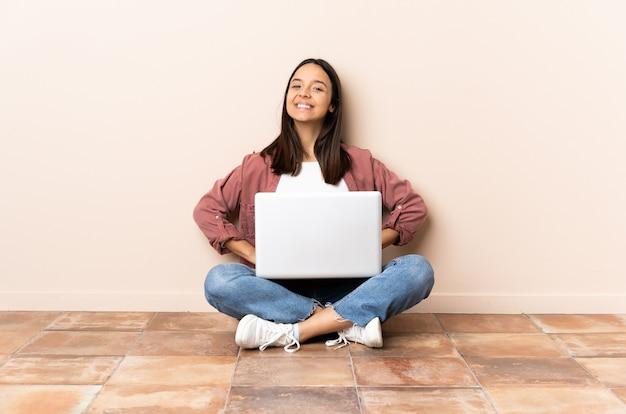 Giovane donna di razza mista con un laptop seduto sul pavimento in posa con le braccia ai fianchi e sorridente