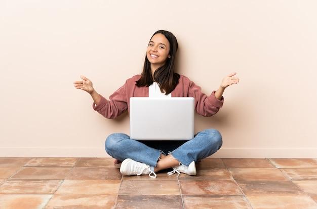 Giovane donna di razza mista con un laptop seduto sul pavimento che presenta e invita a venire con la mano