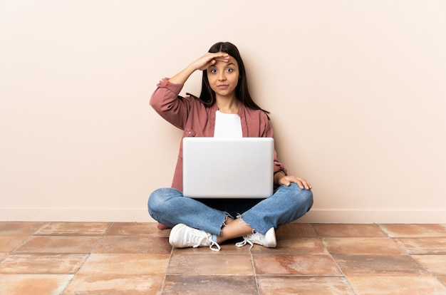 Giovane donna di razza mista con un laptop seduto sul pavimento che saluta