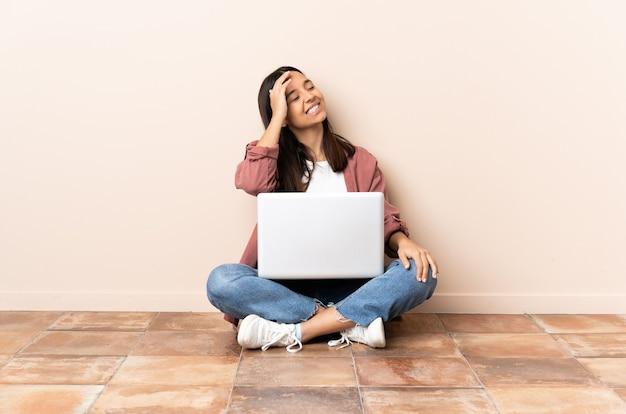 Giovane donna di razza mista con un laptop seduto sul pavimento che sorride molto