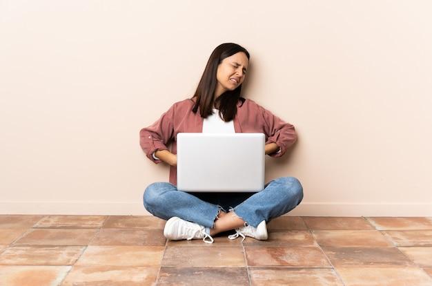 Giovane donna di razza mista con un laptop seduto sul pavimento che soffre di mal di schiena per aver fatto uno sforzo