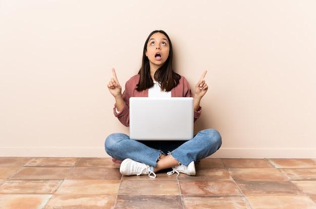 Giovane donna di razza mista con un laptop seduto sul pavimento sorpreso e rivolto verso l'alto