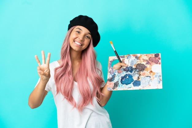 Giovane donna di razza mista con i capelli rosa che tiene una tavolozza isolata su sfondo blu felice e conta tre con le dita