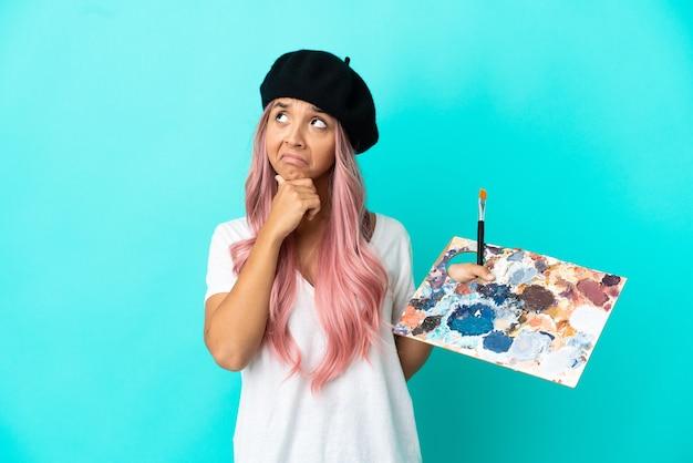Giovane donna di razza mista con i capelli rosa in possesso di una tavolozza isolata su sfondo blu che ha dubbi