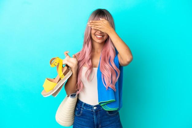 Giovane donna di razza mista con capelli rosa che tiene sandali estivi isolati su sfondo blu che copre gli occhi con le mani. non voglio vedere qualcosa