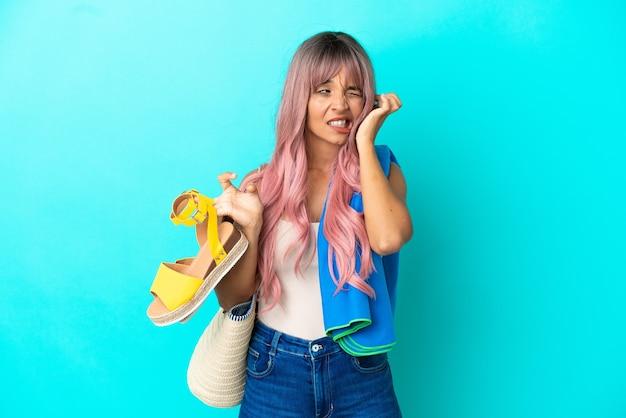 Giovane donna di razza mista con capelli rosa che tiene sandali estivi isolati su sfondo blu frustrata e che copre le orecchie