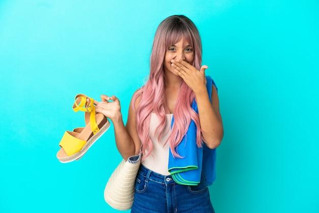 Giovane donna di razza mista con capelli rosa che tiene sandali estivi isolati su sfondo blu felice e sorridente che copre la bocca con la mano
