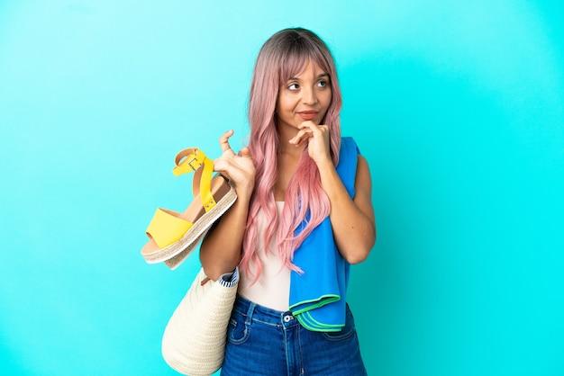 Giovane donna di razza mista con capelli rosa che tiene sandali estivi isolati su sfondo blu avendo dubbi