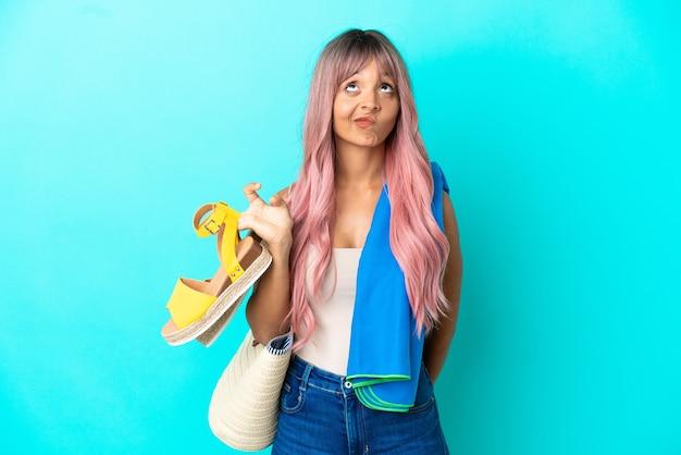 Giovane donna di razza mista con capelli rosa che tiene sandali estivi isolati su sfondo blu e guarda in alto