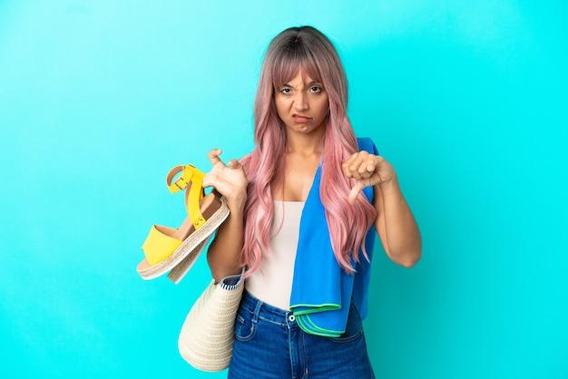 Giovane donna di razza mista con capelli rosa che tiene sandali estivi isolati su sfondo blu che mostra il pollice verso il basso con espressione negativa