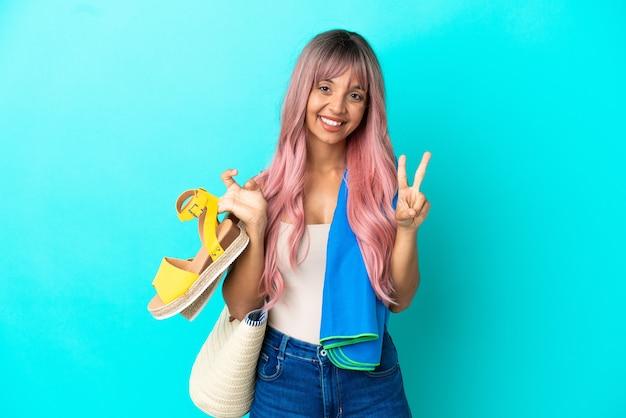 Giovane donna di razza mista con capelli rosa che tiene sandali estivi isolati su sfondo blu che sorride e mostra il segno della vittoria