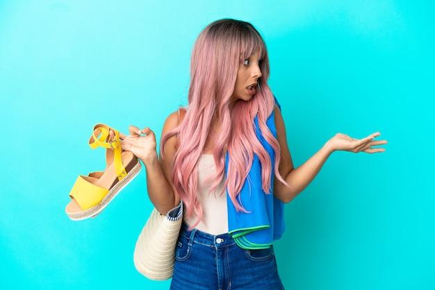 Giovane donna di razza mista con capelli rosa che tiene sandali estivi isolati su sfondo blu con espressione di sorpresa mentre guarda di lato