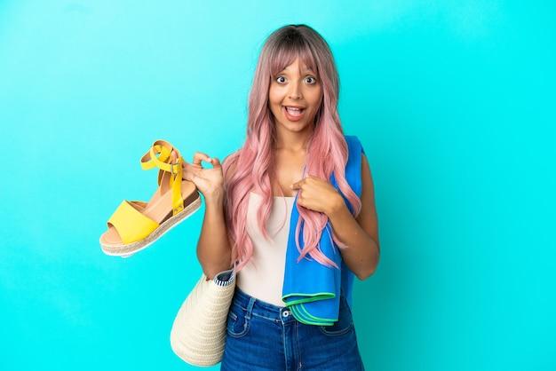 Giovane donna di razza mista con capelli rosa che tiene sandali estivi isolati su sfondo blu con espressione facciale a sorpresa