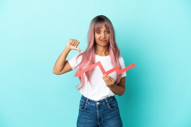 Giovane donna di razza mista con capelli rosa isolata su sfondo blu che tiene una freccia verso il basso e fa un cattivo segnale