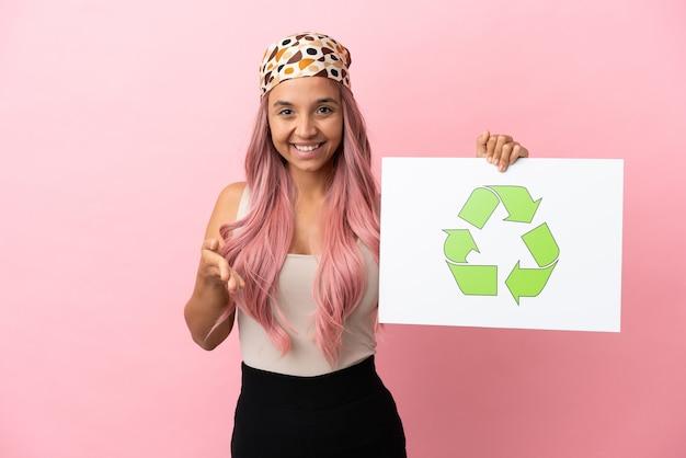 Giovane donna di razza mista con capelli rosa isolata su sfondo rosa con in mano un cartello con icona di riciclo che fa un affare