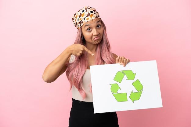 Giovane donna di razza mista con capelli rosa isolata su sfondo rosa che tiene in mano un cartello con l'icona di riciclo e lo indica