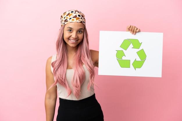 Giovane donna di razza mista con capelli rosa isolata su sfondo rosa con in mano un cartello con icona di riciclo con espressione felice