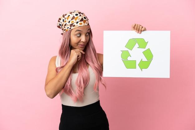 Giovane donna di razza mista con i capelli rosa isolata su sfondo rosa che tiene un cartello con l'icona di riciclo