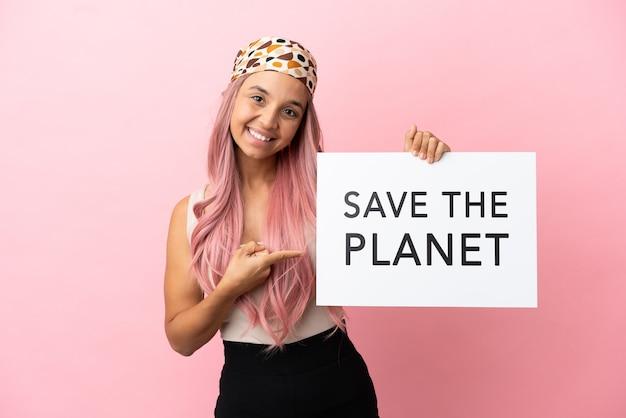 Giovane donna di razza mista con i capelli rosa isolata su sfondo rosa che tiene un cartello con il testo salva il pianeta e lo indica