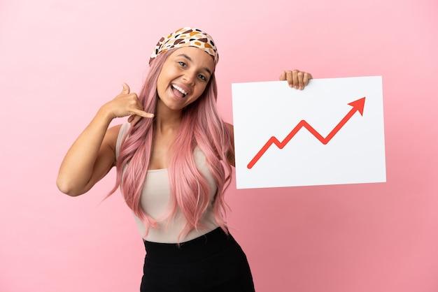 Giovane donna di razza mista con i capelli rosa isolata su sfondo rosa con in mano un cartello con un simbolo di freccia statistica in crescita e che fa il gesto del telefono
