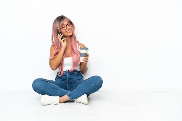 Giovane donna di razza mista con i capelli rosa seduta sul pavimento isolato su sfondo bianco con in mano caffè da asporto e un cellulare