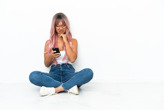 Giovane donna di razza mista con i capelli rosa seduta sul pavimento isolata su sfondo bianco pensando e inviando un messaggio
