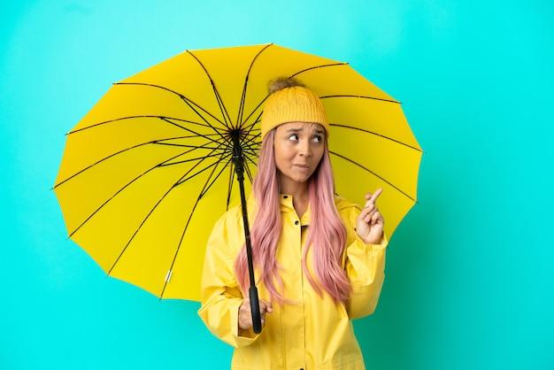 Giovane donna di razza mista con cappotto antipioggia e ombrello con le dita incrociate e augurando il meglio