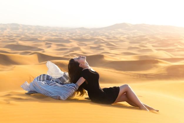 Giovane modella in abito nero in posa sdraiata sulla sabbia nel deserto