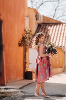 Una giovane ragazza modello in un bellissimo vestito con un mazzo di fiori in campagna in francia. ragazza con fiori nel villaggio della provenza di primavera.