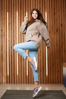 Una giovane ragazza modello in una felpa con cappuccio rosa, blue jeans e scarpe da ginnastica che salta e posa all'interno. una giovane donna in abbigliamento sportivo casual
