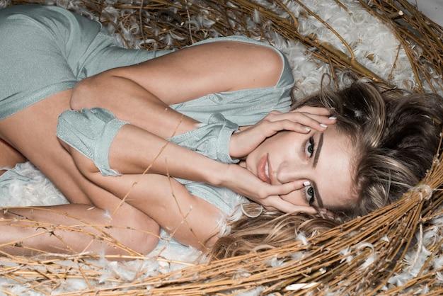 Giovane ragazza modello con un corpo perfetto in lingerie di pizzo alla moda in un enorme nido. avvicinamento. trucco perfetto. stile, donna, studio, arte