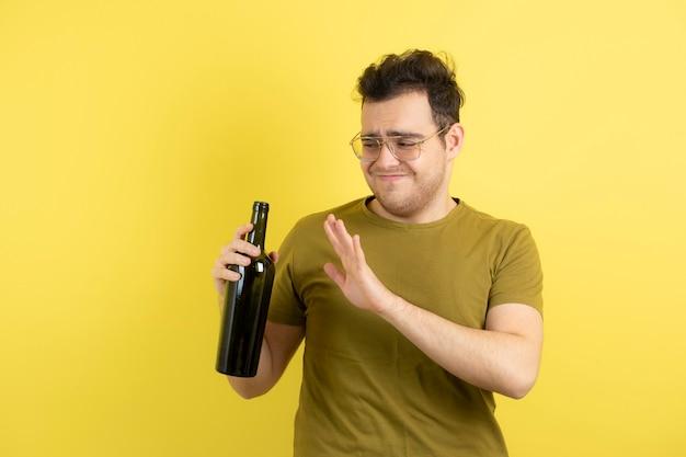 Giovane modello che tiene una bottiglia di vino bianco con espressione disturbata.