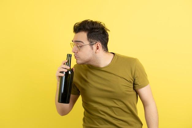 Giovane modello che tiene una bottiglia di vino bianco.