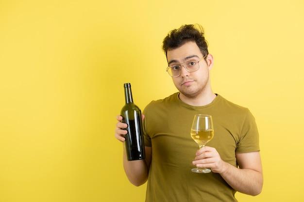 Giovane modello che tiene un bicchiere e una bottiglia di vino bianco.