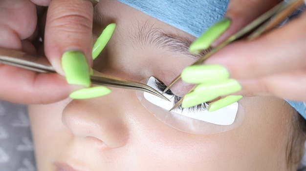 Un giovane modello è sdraiato sulla procedura di estensione delle ciglia le mani del maestro sono vicine tenendo le pinzette e incollando le ciglia