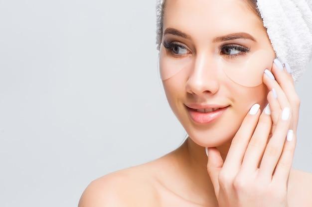 Giovane modella con asciugamano in testa con trattamenti cosmetici