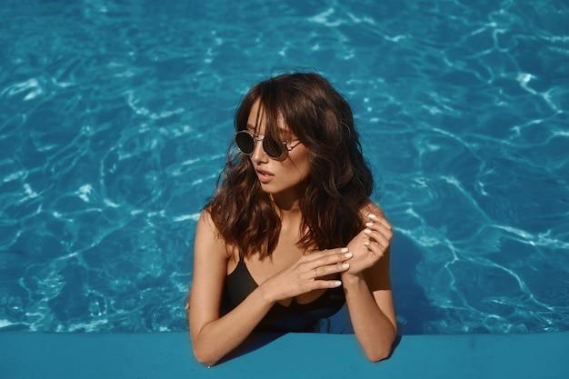 Una giovane donna modello in costume da bagno nero e occhiali da sole alla moda in posa in piscina in una giornata di sole estivo.