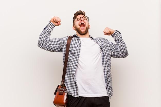 Giovane uomo moderno di affari che alza pugno dopo una vittoria, concetto del vincitore.
