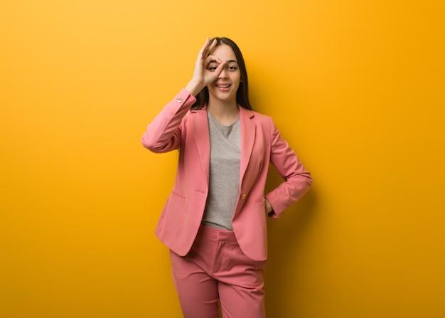 Giovane donna moderna di affari sicura che fa gesto giusto sull'occhio