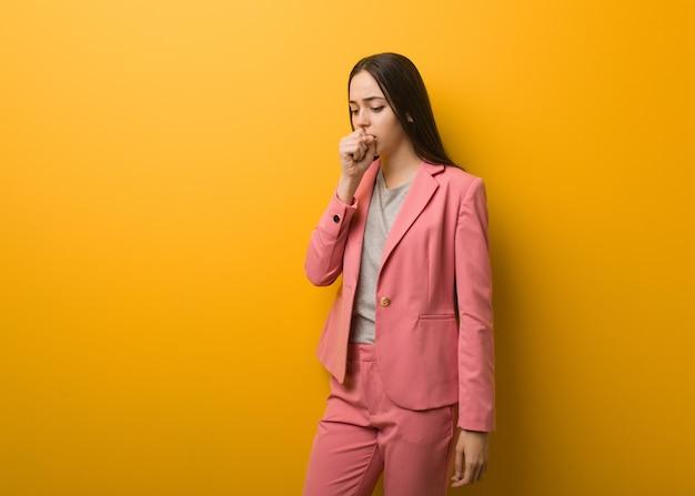 Giovane donna moderna di affari che tossisce, malata a causa di un virus o di un'infezione