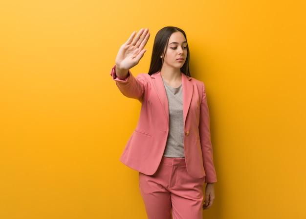 Giovane donna moderna di affari che mette la mano davanti